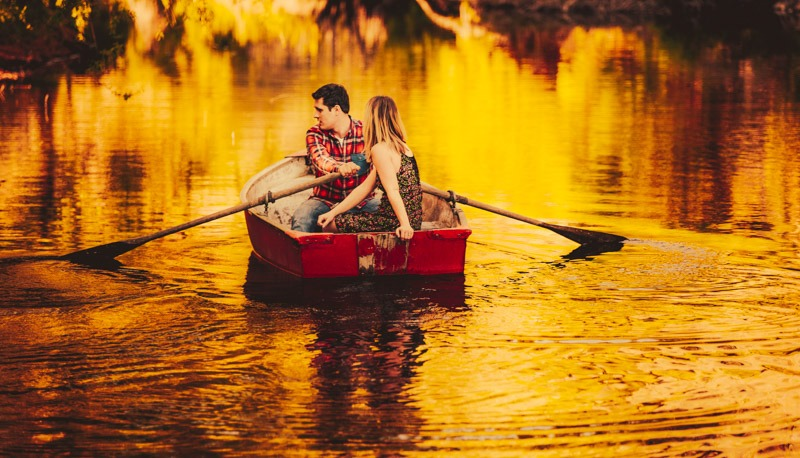 photo of couple in rowboat on golden pond at sunset