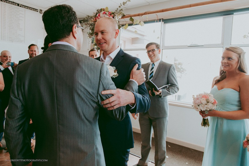 father of bride shaking grooms hand at end of the aisle