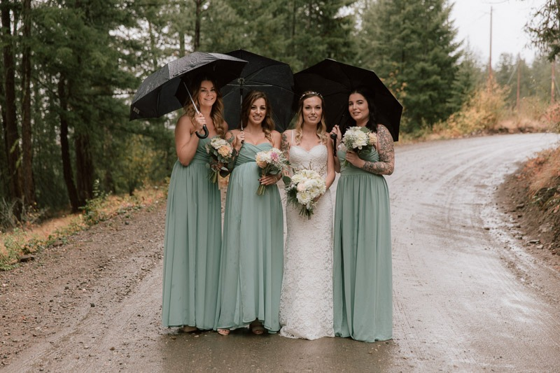 bridal party photos - bride and bridesmaids under umbrellas in this rainy day wedding