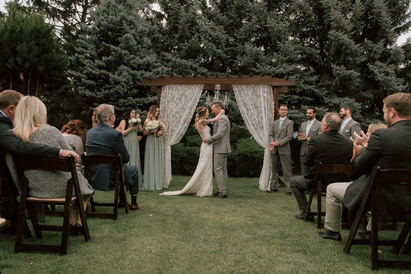 wedding ceremony under archway at durali villa in vernon